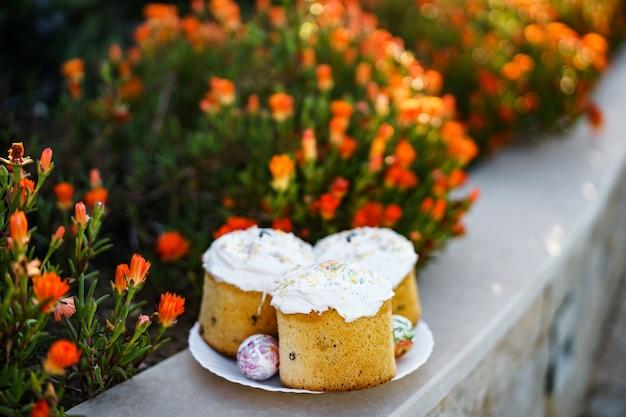Bolos de páscoa em um prato com ovos de páscoa perto de um canteiro de flores
