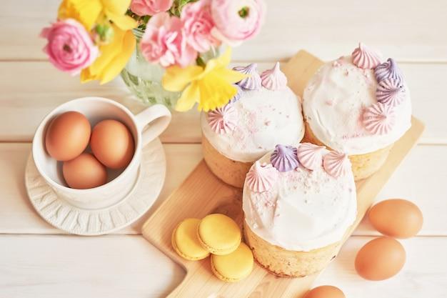 Bolos de páscoa na mesa, biscoitos, ovos e buquê de flores em vaseaster