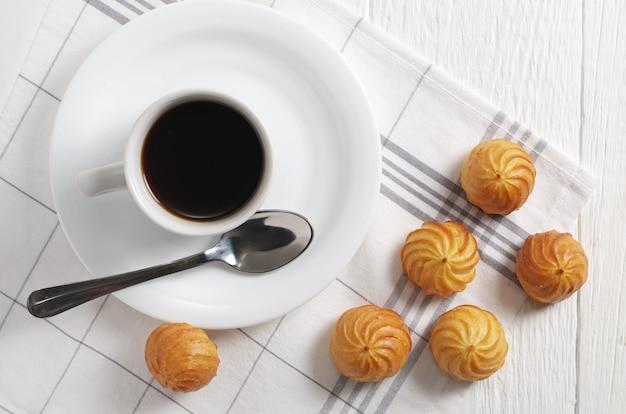 Bolos de pastelaria choux e café em um guardanapo de linho