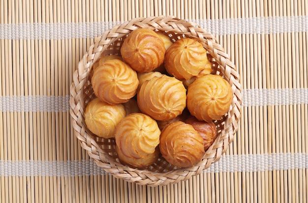 Bolos de pastelaria choux em uma tigela de vime