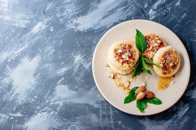 Bolos de queijo com amêndoas hortelã e xarope de bordo em um fundo cinza de uma mesa de concreto.