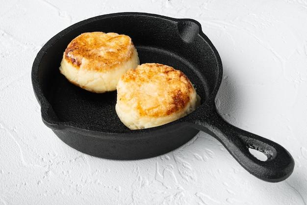 Bolos de queijo panquecas doces na frigideira de ferro fundido na frigideira de ferro fundido, no fundo da mesa de pedra branca