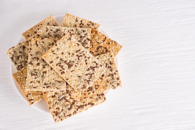 Bolos de trigo crocantes com linho de gergelim e sementes de girassol no prato fundo branco de madeira