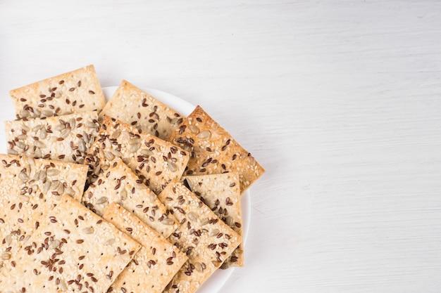 Bolos de trigo crocantes com sementes de gergelim, linho e girassol no prato fundo branco de madeira. comida vegetariana, conceitos de comida ecológica