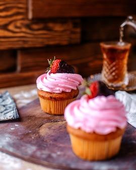 Bolos de vista frontal com creme de rosa e morango, juntamente com chá quente na superfície marrom