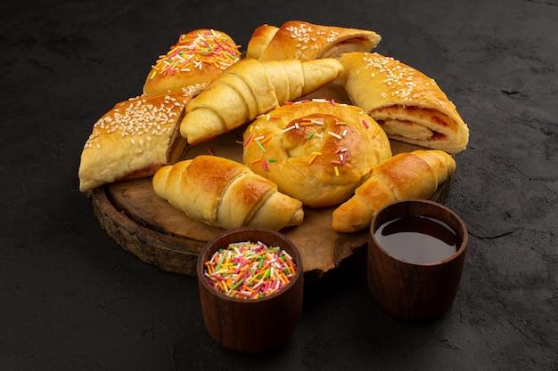 Bolos de vista superior, juntamente com croissants deliciosos doces na mesa marrom e no chão escuro