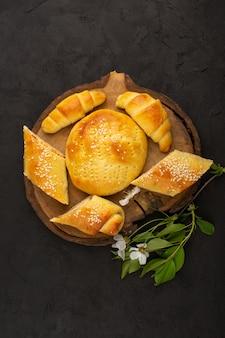 Bolos de vista superior, juntamente com croissants deliciosos na mesa escura