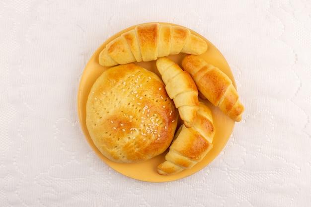 Bolos de vista superior, juntamente com croissants, dentro da placa laranja no chão branco