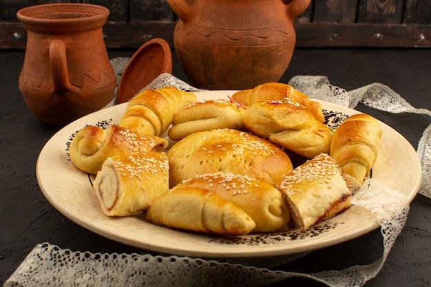 Bolos de vista superior, juntamente com deliciosos croissants dentro de chapa branca no chão escuro