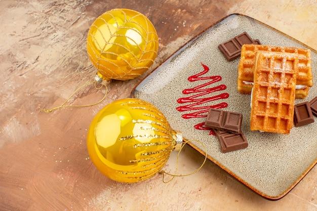 Bolos de waffle deliciosos de frente com brinquedos de árvore de ano novo em fundo claro torta doce creme sobremesa bolos