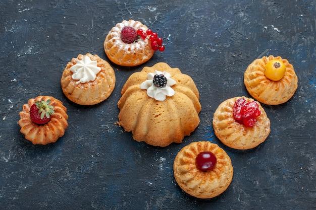 Bolos deliciosos diferentes assados com creme e frutas vermelhas no escuro, baga bolo de biscoito doce