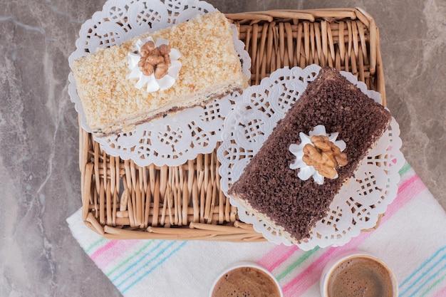 Bolos deliciosos e xícaras de café na toalha de mesa.