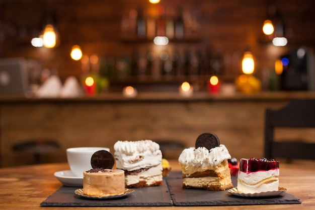 Bolos diferentes com creme de pudim na mesa de madeira em uma cafeteria. bolo de pudim com frutas vermelhas frescas por cima. saborosa xícara de café.