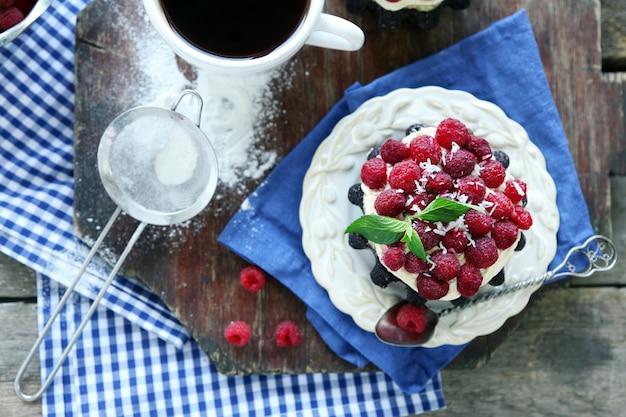 Bolos doces com framboesas na mesa de madeira