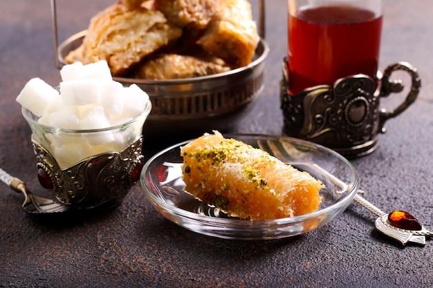 Bolos doces de baklava para sobremesa servidos com chá em mesa escura