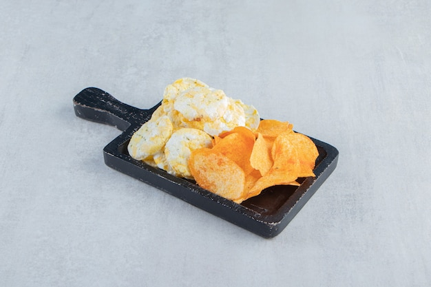 Bolos e batatas fritas de arroz integral crocante na placa de corte preta.