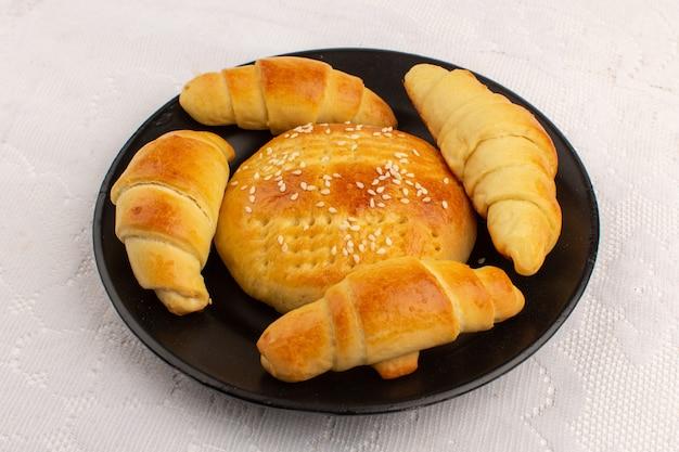 Bolos e croissants de vista superior deliciosos gostoso dentro de chapa preta no chão branco