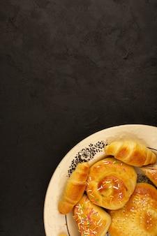 Bolos e croissants de vista superior dentro de chapa branca sobre o fundo escuro