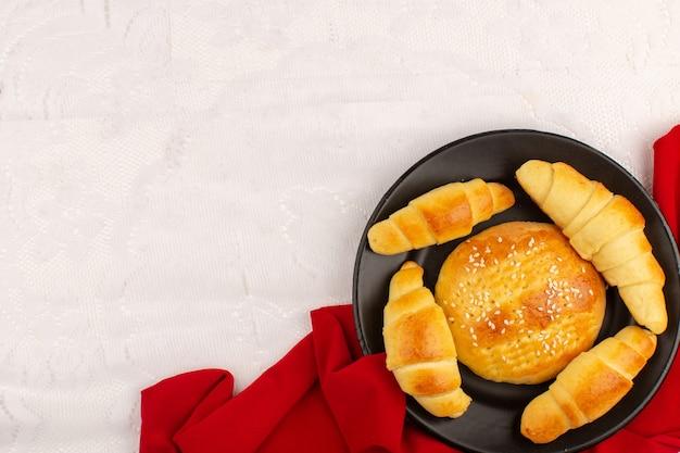 Bolos e croissants de vista superior dentro de chapa preta sobre fundo branco