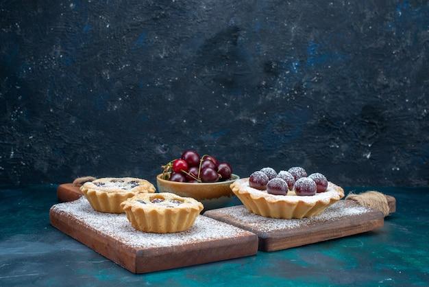 Bolos e frutas em uma mesa azul escura, bolo de frutas cor de biscoito leve ao açúcar doce