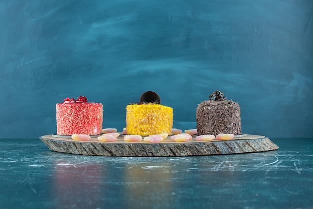 Bolos e marmeladas alinhados em uma placa de madeira em azul.