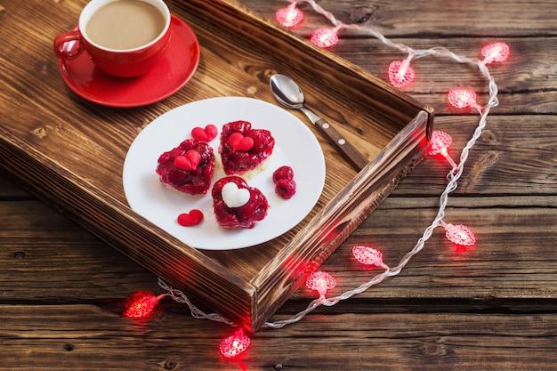 Bolos em forma de coração e xícara de café na mesa de madeira