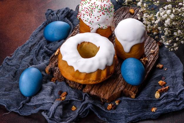 Bolos festivos com esmalte branco, nozes e passas com ovos de páscoa na mesa festiva