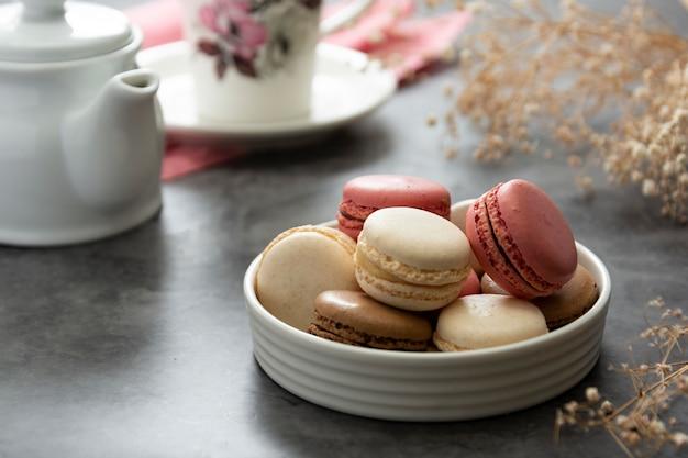 Bolos franceses do macaron em um fim da placa acima. creme, marrom, rosa, macarons.