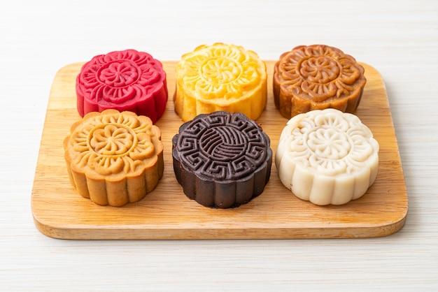 Bolos lunares chineses coloridos com sabores mistos em prato de madeira