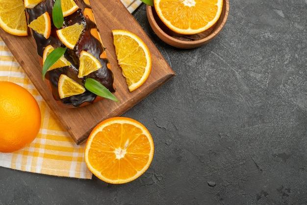 Bolos moles inteiros e laranjas cortadas com folhas na mesa escura