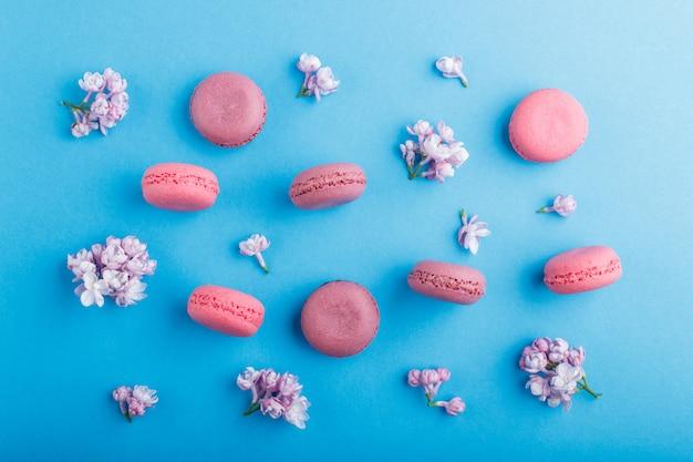 Bolos roxos e cor-de-rosa do macaron ou do bolinho de amêndoa com as flores lilás no azul pastel.