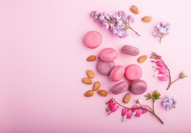 Bolos roxos e cor-de-rosa do macaron ou do bolinho de amêndoa com o coração do lilás e de sangramento floresce no rosa pastel.