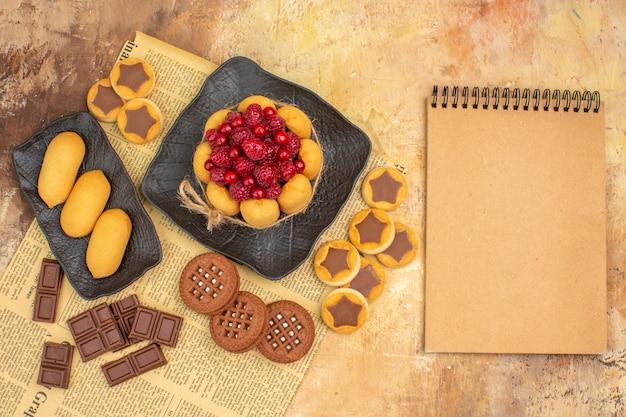 Bolos saborosos, biscoitos diferentes no prato marrom e caderno na mesa de cores misturadas