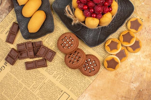 Bolos saborosos, biscoitos diferentes no prato marrom na mesa de cores diferentes