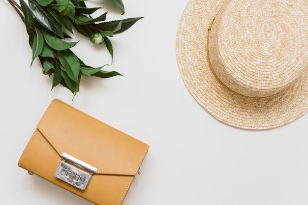 Bolsa amarela, planta e chapéu de palha em um fundo bege