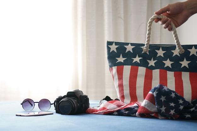 Bolsa americana no hotel em nova york com câmera de acessórios de viagem, óculos de sol
