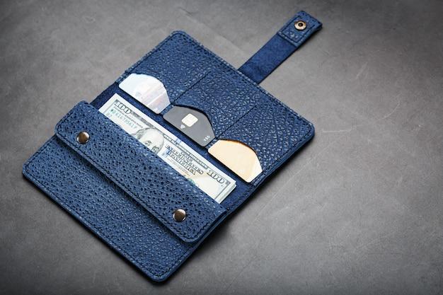 Bolsa azul com notas e cartões de crédito em uma parede preta