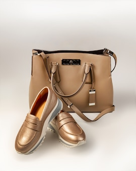 Bolsa bege e um par de sapatos de ouro rosa