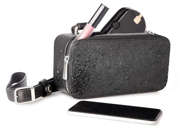 Bolsa brilhante preta com cosméticos e smartphone em branco