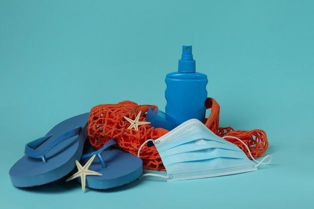 Bolsa com acessórios marinhos, protetor solar e máscara em fundo azul isolado