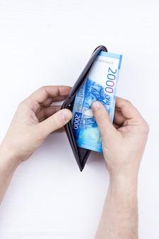 Bolsa com dinheiro em mãos
