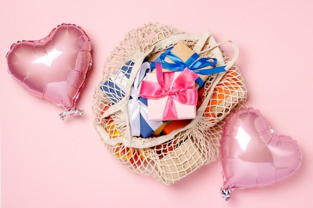 Bolsa com presentes coloridos e vista superior de balões
