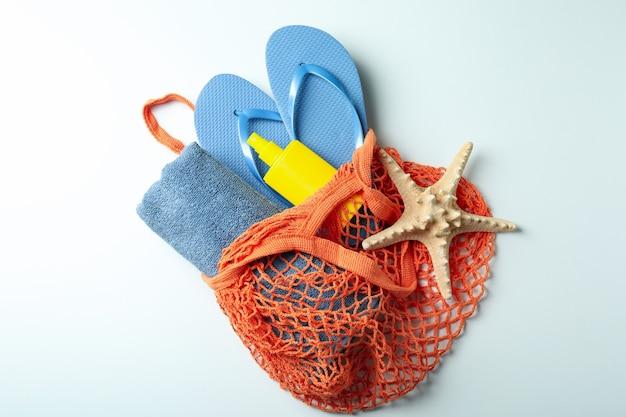 Bolsa com protetor solar, chinelos, toalha e estrela do mar em fundo branco isolado