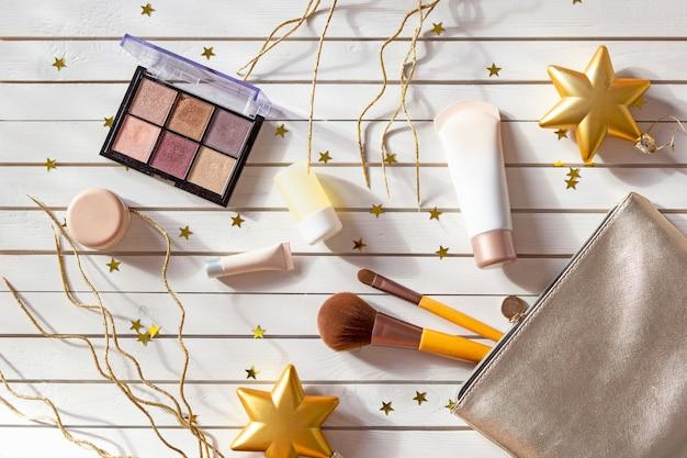 Bolsa cosmética com maquiagem, sombras, pincéis de rosto, cremes e loções no natal com estrelas douradas.