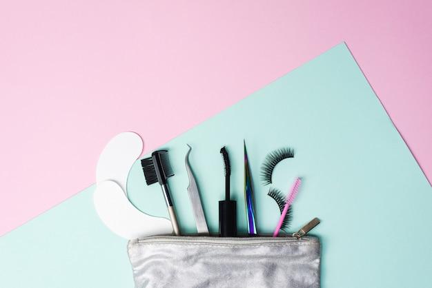 Bolsa cosmética prata com um conjunto para extensão dos cílios e tingimento. pinças de extensão dos cílios, cílios postiços, tapa-olhos e escova de sobrancelha