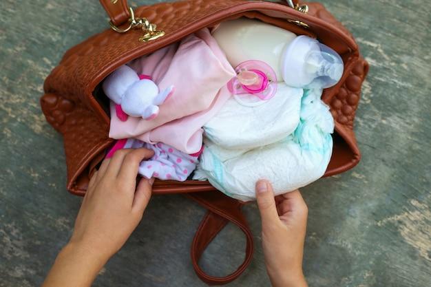 Bolsa da mãe com itens para cuidar de criança. as mãos das mulheres tiram as coisas da bolsa.
