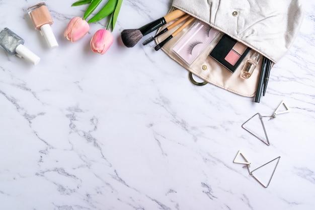 Bolsa de acessórios de cosméticos e mulheres na mesa de mármore, espaço de cópia, vista superior.