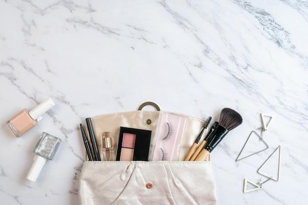 Bolsa de acessórios de cosméticos e mulheres no fundo de mármore, espaço de cópia, vista superior.