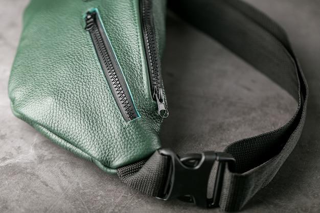 Bolsa de cinto de couro texturizado verde escuro, banana em uma mesa cinza.
