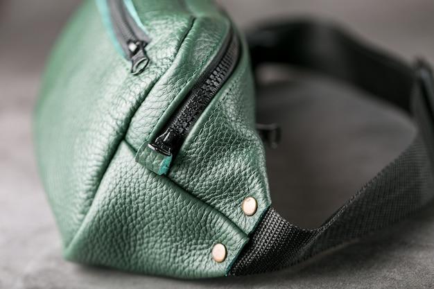 Bolsa de cinto de couro texturizado verde escuro sobre cinza